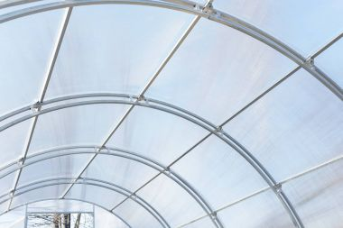 Greenhouse made of polycarbonate and metal carcass. Small hothouse for private use. Metal construction covered with transparent polycarbonate.