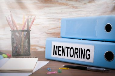 Mentoring, Office Binder on Wooden Desk. On the table colored pencils, pen, notebook paper