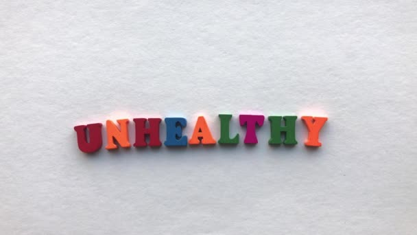 healthy. coloured wooden letters on a white sheet of paper