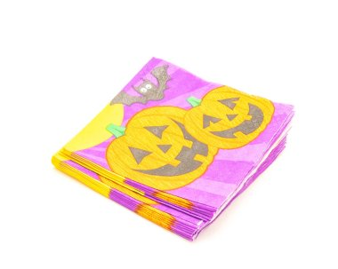 Top view stack of friendly Halloween napkins isolated on white background. Festive party tissue piles display pumpkins, bats, jack-o-lantern