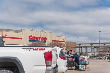 TEXAS, ABD-Mart 21, 2020: Bir Amerikalı aile, ihtiyaç duyulan alışveriş arabalarının bagajlarına yiyecek yükler. Lewisville, Teksas 'taki Costco toptancısının önündeki otoparktan görüntü