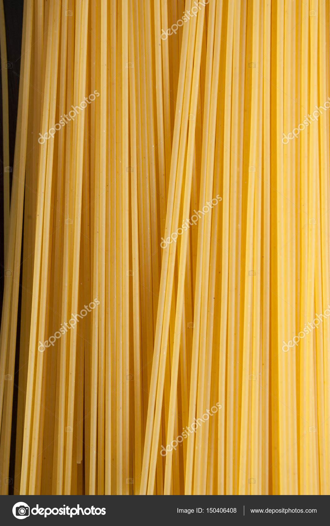 Gele lange spaghetti op zwarte achtergrond. Dunne pasta gerangschikt ...