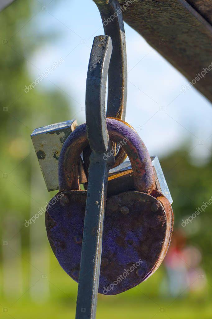Vintage colorful padlocks heart shaped on blurred background, symbol of love