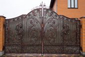 Forged gates for cars in the courtyard of a private house with a decorative scorpion element
