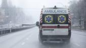 Fotografie Krankenwagen mit eingeschaltetem Blaulicht sind mit hoher Geschwindigkeit auf der Straße unterwegs. Schlechtes Wetter, Regen mit Schneeregen.