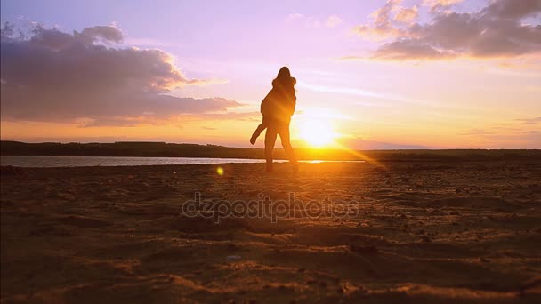 in love with a man circling girl in his arms on background of sunset, silhouettes of people on background of blue sky