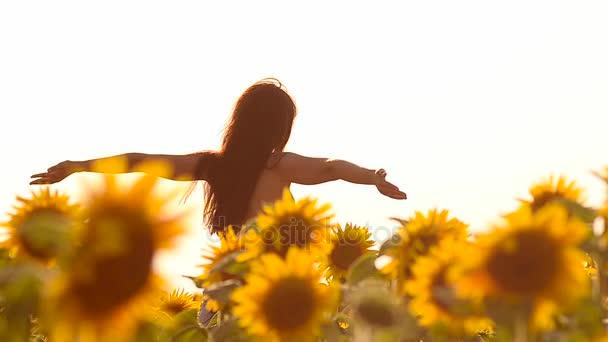 šťastná dívka s vlasy ve větru, chůze v žluté slunečnice, pole zlaté květy, letní slunečný den