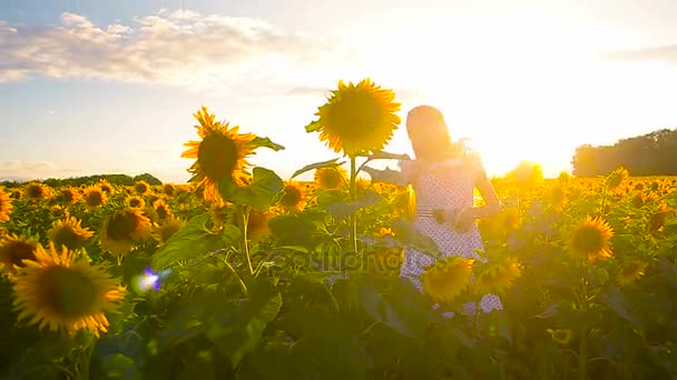 cheerful girl dancing with a phone in a field of yellow sunflowers, teenage girl dancing in a field of golden flowers in sun.