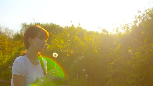 pampelišky létání na slunci, dívka foukání na Pampeliška květ, odpočívat na jaře parku.