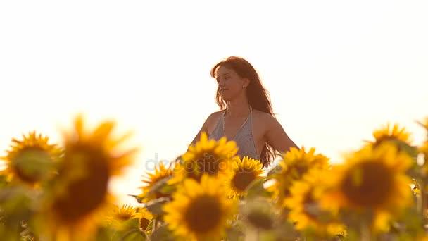 gyönyörű lány haját szél, repülő, sétál a mező sárga napraforgó, gyönyörű mezőben arany színek, megvilágított a nap.