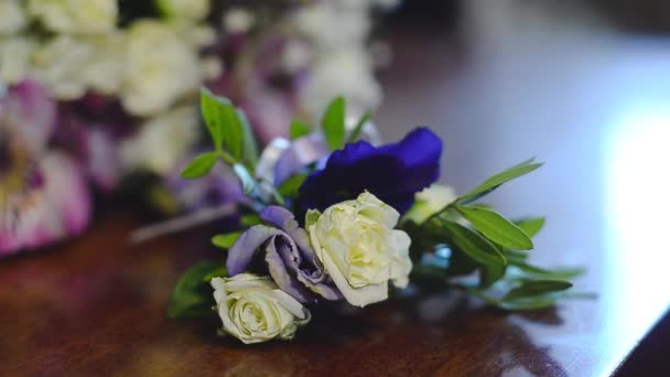 bouquet of white and blue flowers on the table, a man takes in his hand a beautiful colorful flowers.