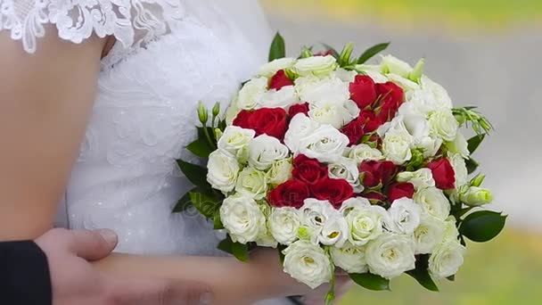 Kytice z červených a bílých růží v rukou nevěsty, dívka v bílé šaty stojí s různobarevné květy v rukou