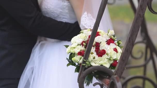 ženicha všeobjímající nevěsty, nevěsta drží kytici červených a bílých růží