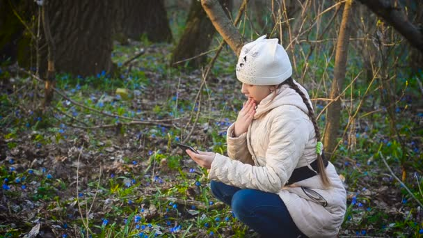 Girl in spring forest on background of snowdrops flower, girl photographed phone spring flowers.