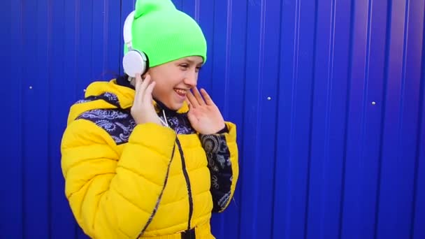 girl with headphones singing and dancing to music, smiling happy girl listening music in headphones.