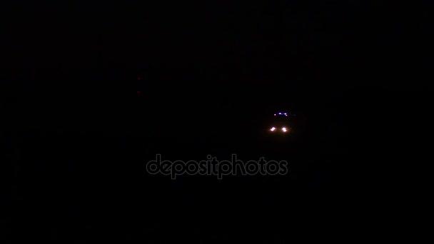 Auto záchranáři náklaďák blikající modré světlo v noci, požární vůz jezdí po silnici s rozsvícenými světly a siréna.