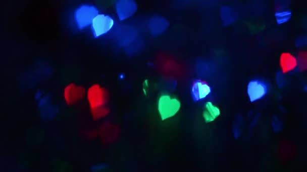 Vícebarevný cyklický blikající kontrolky na tmavém pozadí, rozostření barevná světla, zářící modré červené zelené světlo v temné, lehké sváteční dekorace.