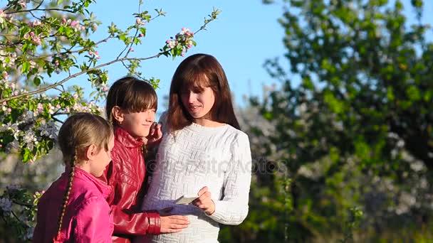 Těhotná maminka a dcera, fotit jsem s telefonem v rozkvetlé Jaro Park, matkou a dětmi Prohlíûení obrázkÛ na dotykové obrazovce v smartphone