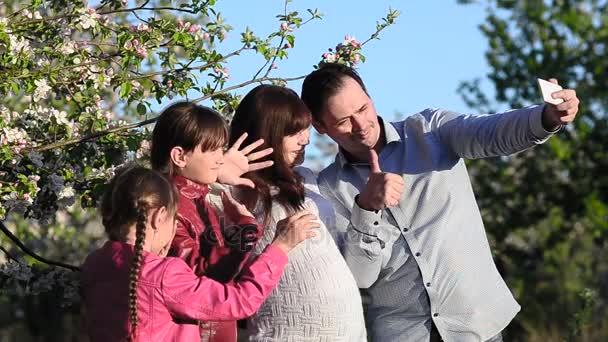 Těhotné Máma, táta a dcera fotografování jsem s telefonem v rozkvetlé Jaro Park, matkou a dětmi Prohlíûení obrázkÛ na dotykové obrazovce v smartphone