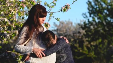 Pregnant mother hugging daughter in blossomed spring Park. Daughter hugs belly of a pregnant mother.