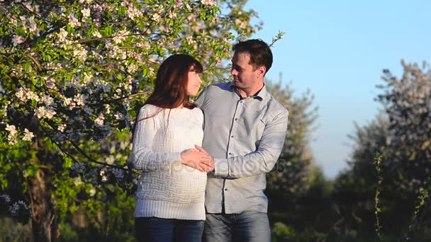 pregnant girl and man show class, husband hugging pregnant wife in flowered Park in spring