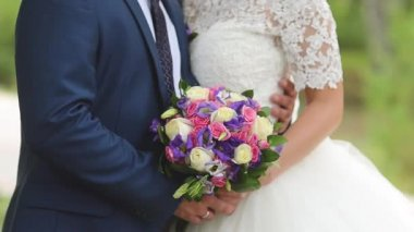 Girl with flowers in white dress hugging man, bouquet of multicolored roses in hands of bride