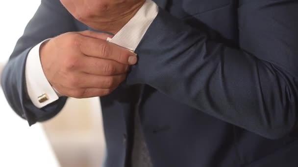 muž v obleku upraví jeho rukávy bílé košile.