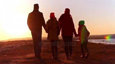 Happy family walking on coast bay. Family walking on sea coast. Silhouettes sunset.