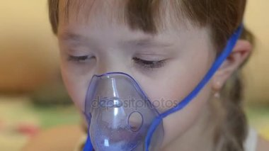 Sick girl in mask for inhalation, girl in hospital is treated by inhalation.