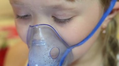 Girl in hospital is treated with inhalation, sad child in hospital breathing mask for inhalation.