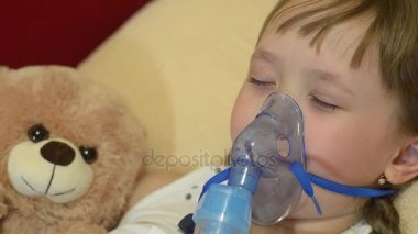Sick girl sleeps with soft toy, girl in hospital being treated for inhalation.