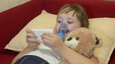 Girl is treated with inhalation, child plays in phone, hugging his favorite toy.
