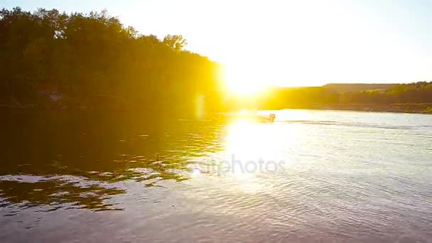motorový člun plováky na řece v krásných paprsky slunce, siluety jachty v západu slunce plovoucí dolů po řece