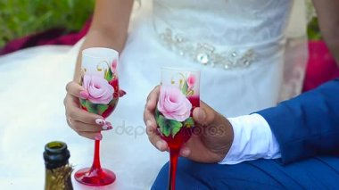 Glass of wine in hands of bride and groom, the sound of wedding glasses