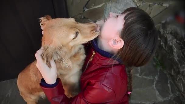 pes pozdraví vlastníka u dveří, dospívající dívka hraje se psem, pes olizuje obličej dívka