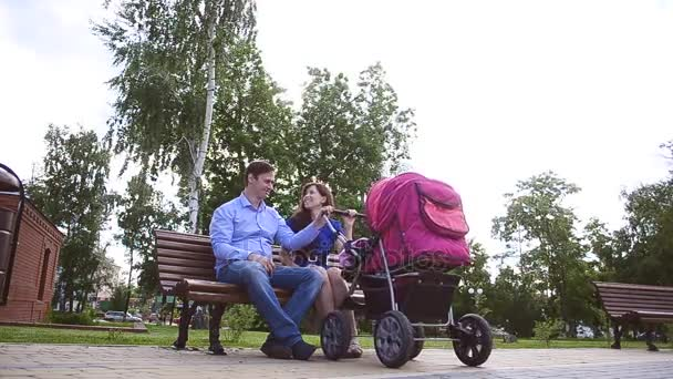 Dad and mom are sitting on bench with baby stroller in park, family holiday on day off in the summer.