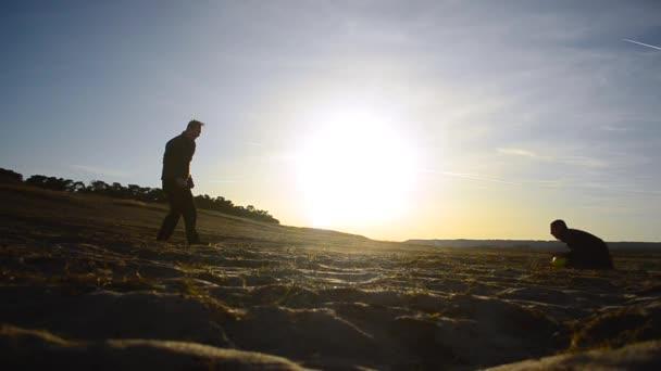 a férfiak futballozni, a strand a tavaszi sziluettek rúgni egy futball-labda, a kapus elkapja a labdát