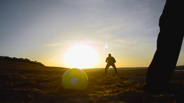 siluety mužů hrajících fotbal na pláži, kick fotbalový míč, brankář chytí míč