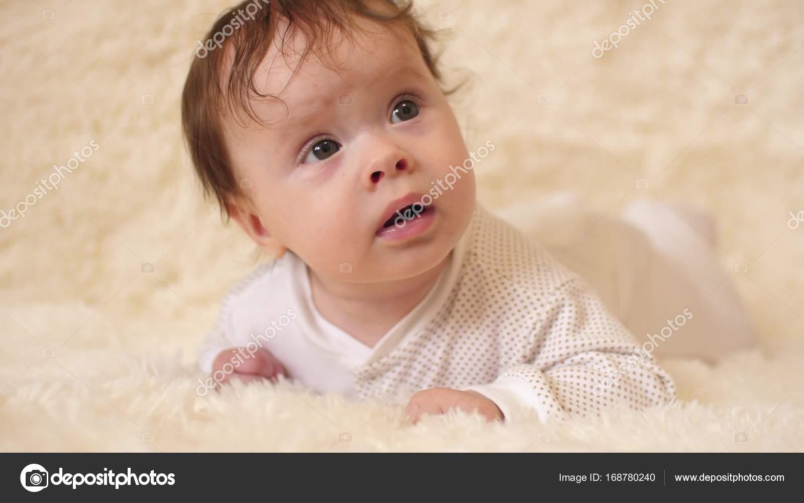 hermoso bebé acostado sobre el estómago en la cama y sonriendo ...