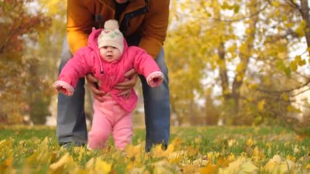 Dítě s jeho otec chůze s nohama na podzimní listí.