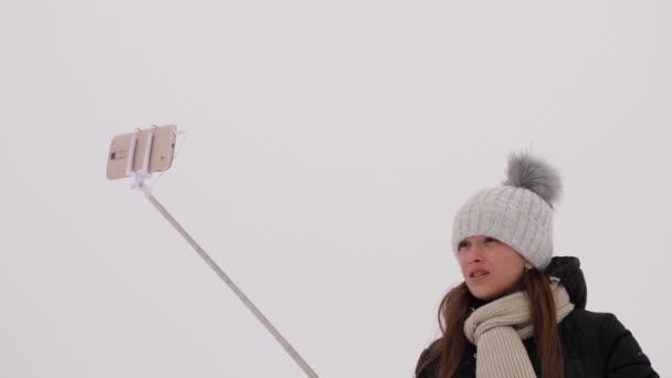 Krásná dívka fotografování selfie na telefonu, zimní snow park