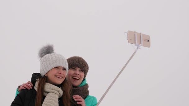 Máma s dcerou, selfie fotografii na telefonu, zimní snow park.