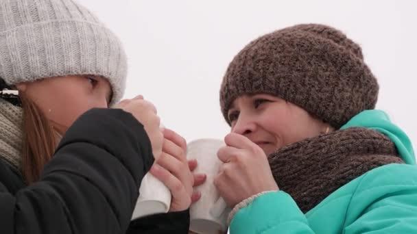 Máma a dcera pít kávu a čaj z bílého skla, mluví, směje se a s úsměvem