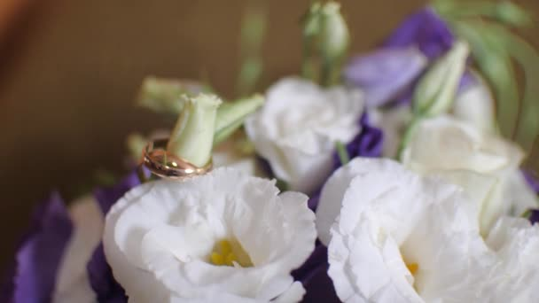 gold wedding rings weigh on a multicolored bouquet of flowers
