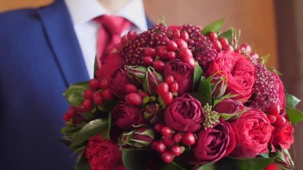 muž v saku a červená je krásná kytice z červených růží drží v ruce