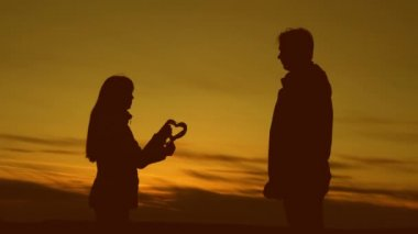 Man and woman are holding love heart at sunset.