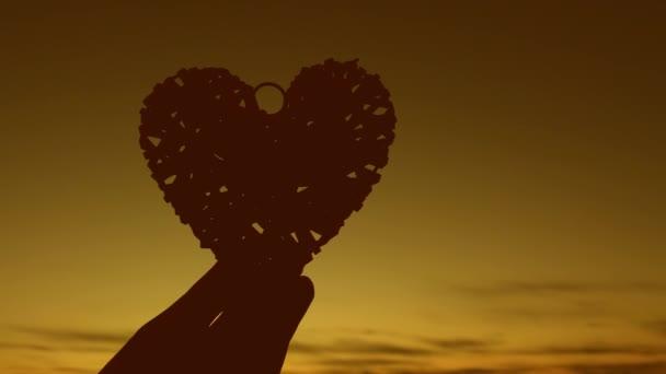 Dívka drží srdce v západu slunce. Samota je smutná vzpomínka.