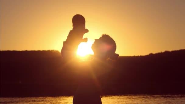 Baby und Mutter zusammen bei Sonnenuntergang rote Sonne. Zeitlupe.