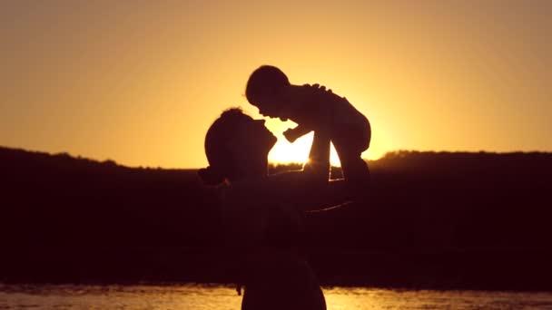 Mutter wirft Baby über roten Sonnenuntergang Zeitlupe.