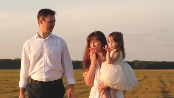 Šťastné dítě posílá pusu mámě a tátovi. Dítě líbá milovanou matku a otce, jak se procházejí po poli na slunci. Šťastná mladá rodina. Koncept šťastné rodiny